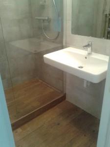 Łazienka z odpływem liniowym, gres drewnopodobny na podłodze / Kafelkarz Gdańsk
